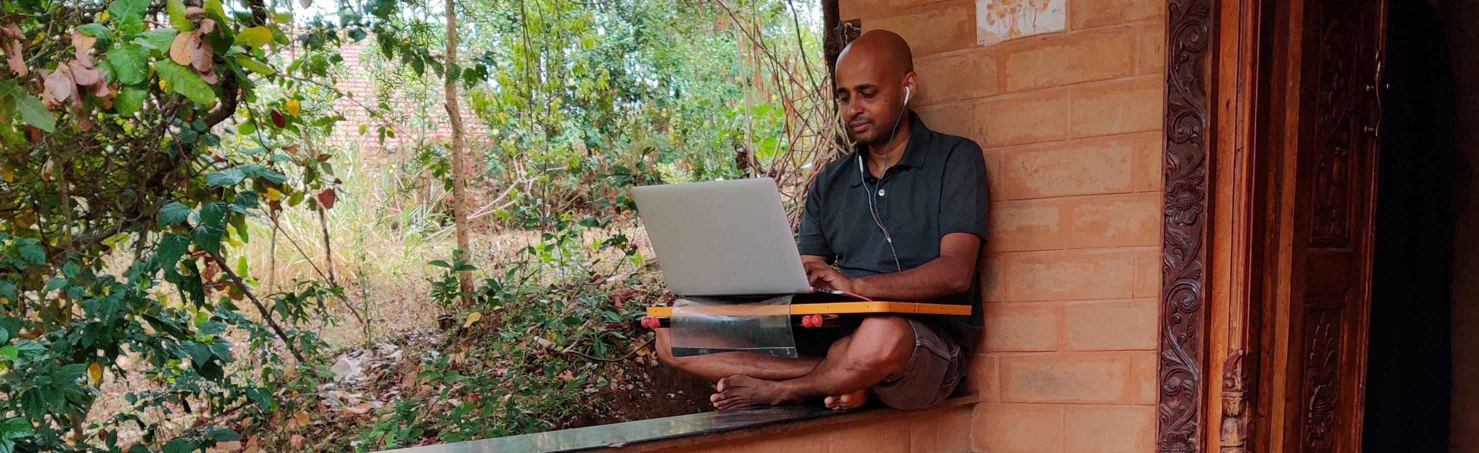 Photo of a man sitting on his porch, working on a laptop in remote India