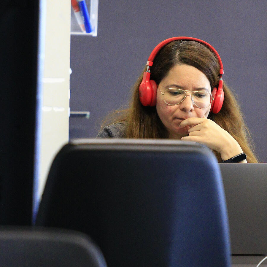 Image of a ThoughtWorker listening to something on her laptop and headphones