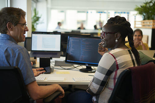 Two ThoughtWorks employees sitting at a desk talking to each other, with a computer screen full of code visible between them.