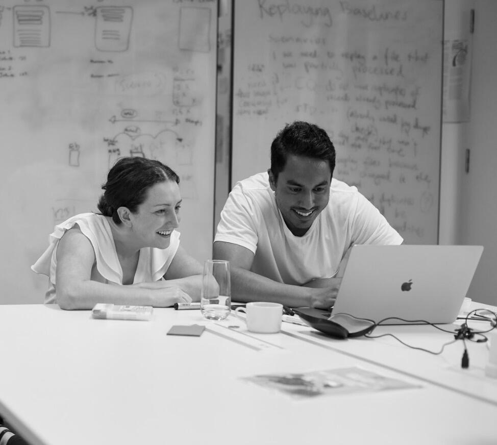 Two ThoughtWorkers chatting across a laptop