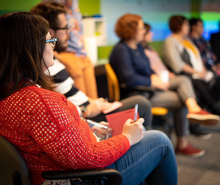 Profile image of a group of Thoughtworkers listening to a presentation. Woman closest to the camera in focus.